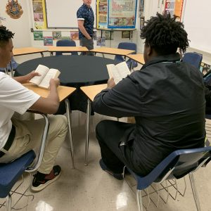 Three students reading aloud in literature class