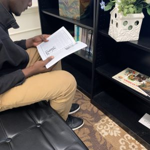 High school student reading a book while sitting